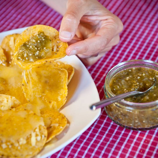 Hot and spicy Mexican salsa verde goes down a treat with corn chips and cheese.(© All Rights Reserved)